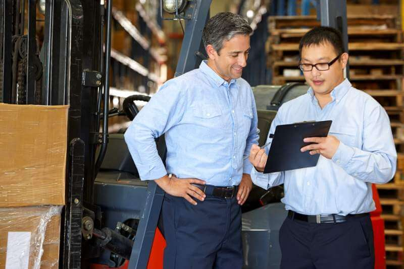 businessmen-meeting-by-fork-lift-truck-in