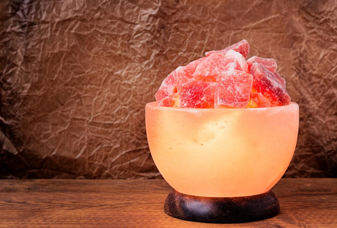 Pink Himalayan salt lamp on wooden table