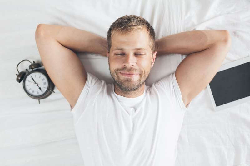 man-sleeping-on-bed-after-using-his-digital