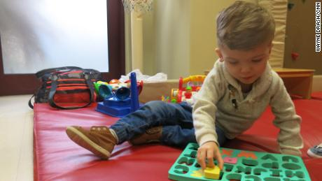 Jadon plays with letters of the alphabet during a physical therapy session.