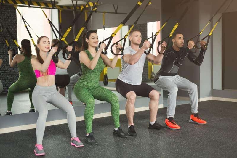 group-performing-trx-suspension-training-in-gym