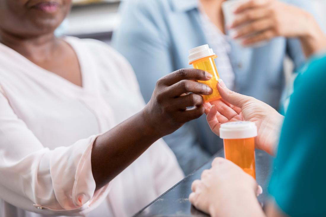 doctor or pharmacist giving prescription medication pill bottle to patient for ulcerative colitis treatments