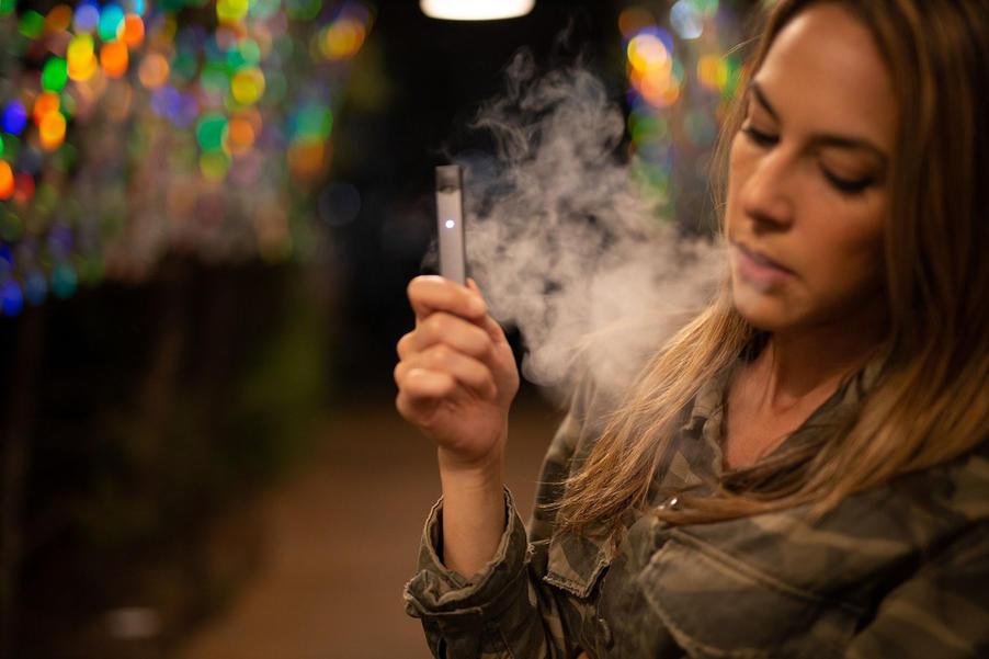 young girl vaping and blowing smoke