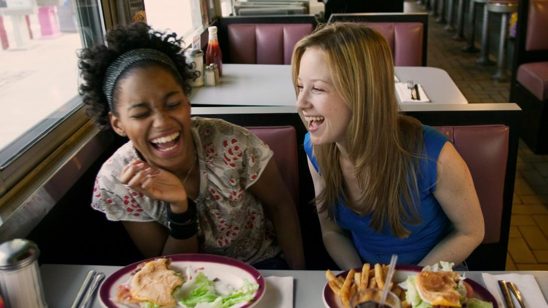 Two teenage girls laughing as they talk about the stages of puberty