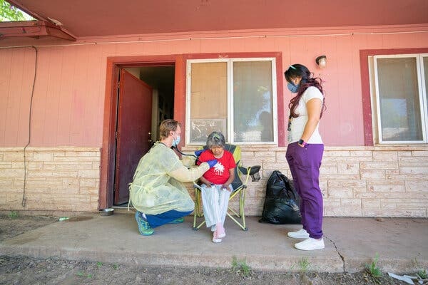 Dr. Ryan Close, left, an Indian Health Services physician, and J.T. Nashio, a community health worker, checked on Judie Declay, who lives on the Fort Apache reservation.